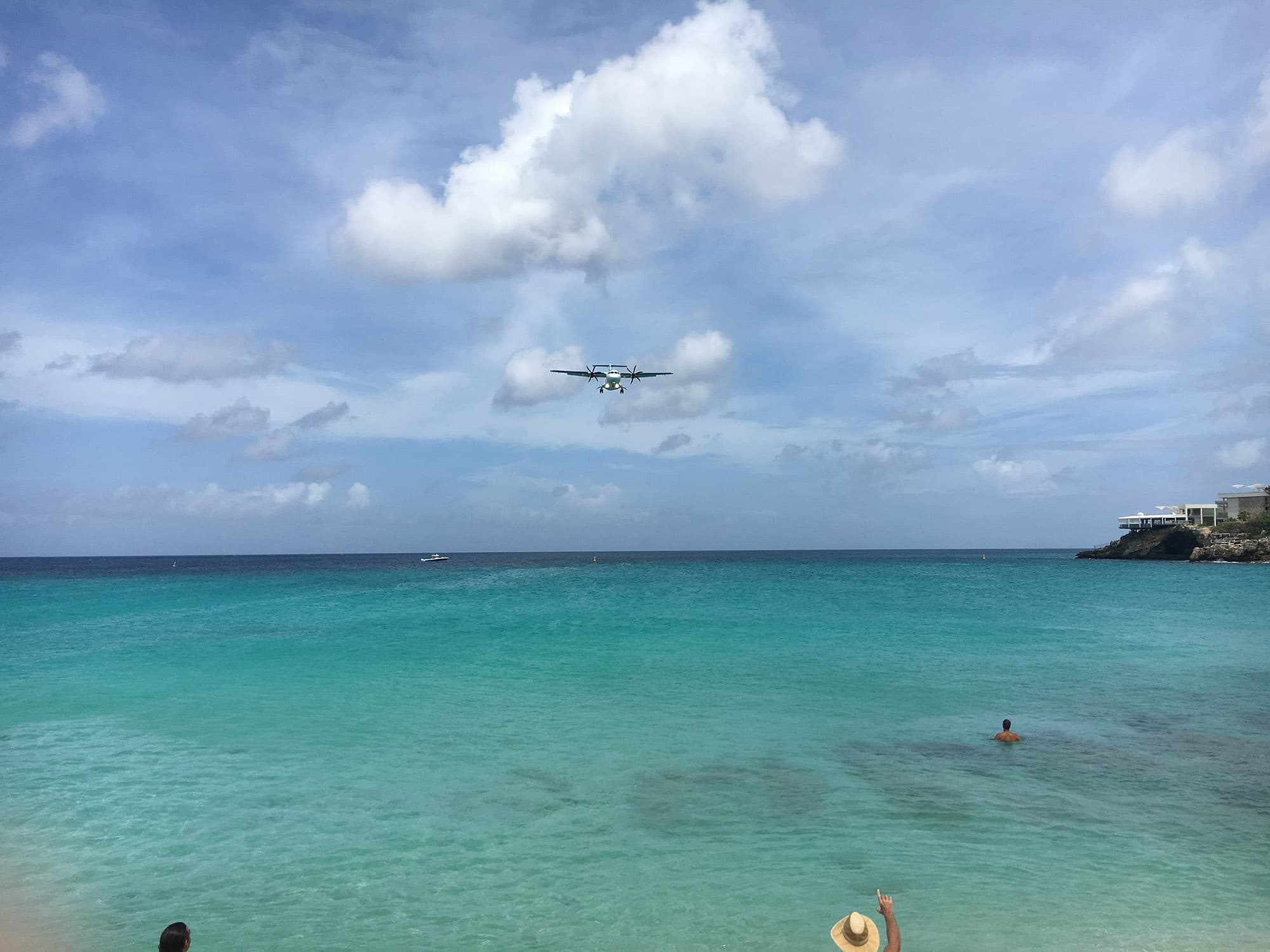 Maho Beach St Maarten - BEFORE EDITING! smartphone editing tips, smartphone editing tutorial, smartphone photography tips, smartphone photography tricks, smartphone photography tutorials _ Last year I made an amazing journey sailing from Colombia to Portugal on the Nomad Cruise. On the way, we made one stop on Saint Maarten Island in the Caribbean. The island itself is not the most interesting place but I did want to go to the beach where the planes fly over. I'm always trying to make photos of this kind of touristic hotspots a little bit different. So I positioned myself in such a way that all the tourists on the beach would be out of my frame. When I saw this guy with the hat I knew that would be my shot. Later when I checked the image on my phone I felt a little disappointed. The photo did not reflect my experience of being on that beach at all. It has a couple of flaws. Most embarrassing one being my finger in front of the lens. But that is not the only thing. The colors and contrasts are flat and there are more distracting elements. But I could see the potential. So I started to edit the image in Snapseed to make it come alive.