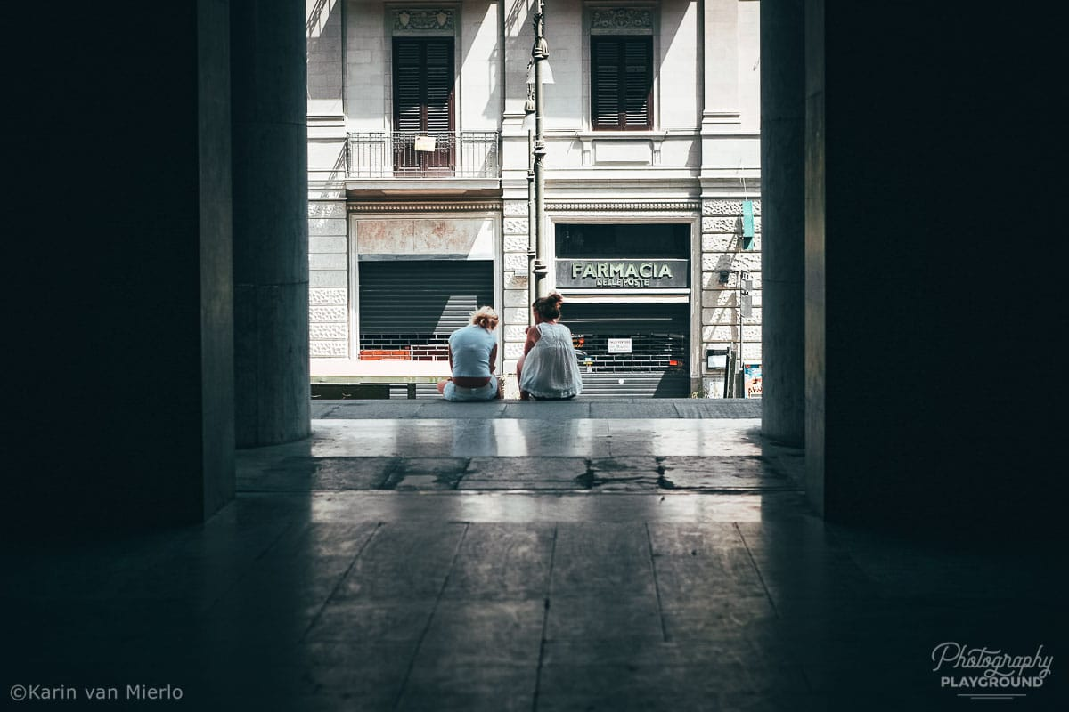principles of composition in photography, photo composition examples, composition techniques, composition rules, frame within a frame | Copyright Karin van Mierlo for Photography Playground. Photo: 2 girls sitting at the sidewalk of the post office in Palermo, Italy.