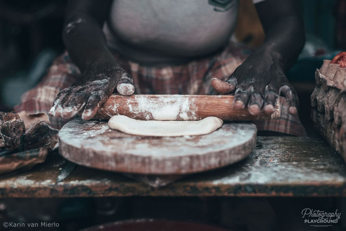 principles of composition in photography, photo composition examples, composition techniques, composition rules, fill the frame | Copyright Karin van Mierlo for Photography Playground. Photo: A woman kneading dough in Kampala, Uganda.