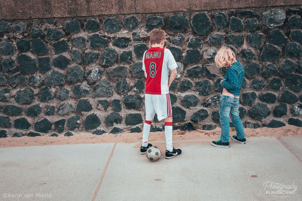photographing children, photographing kids, child photography tips, tips for photographing kids, how to photograph kids | Photo: 2 brothers peeing against a wall Copyright Karin van Mierlo | Photography Playground