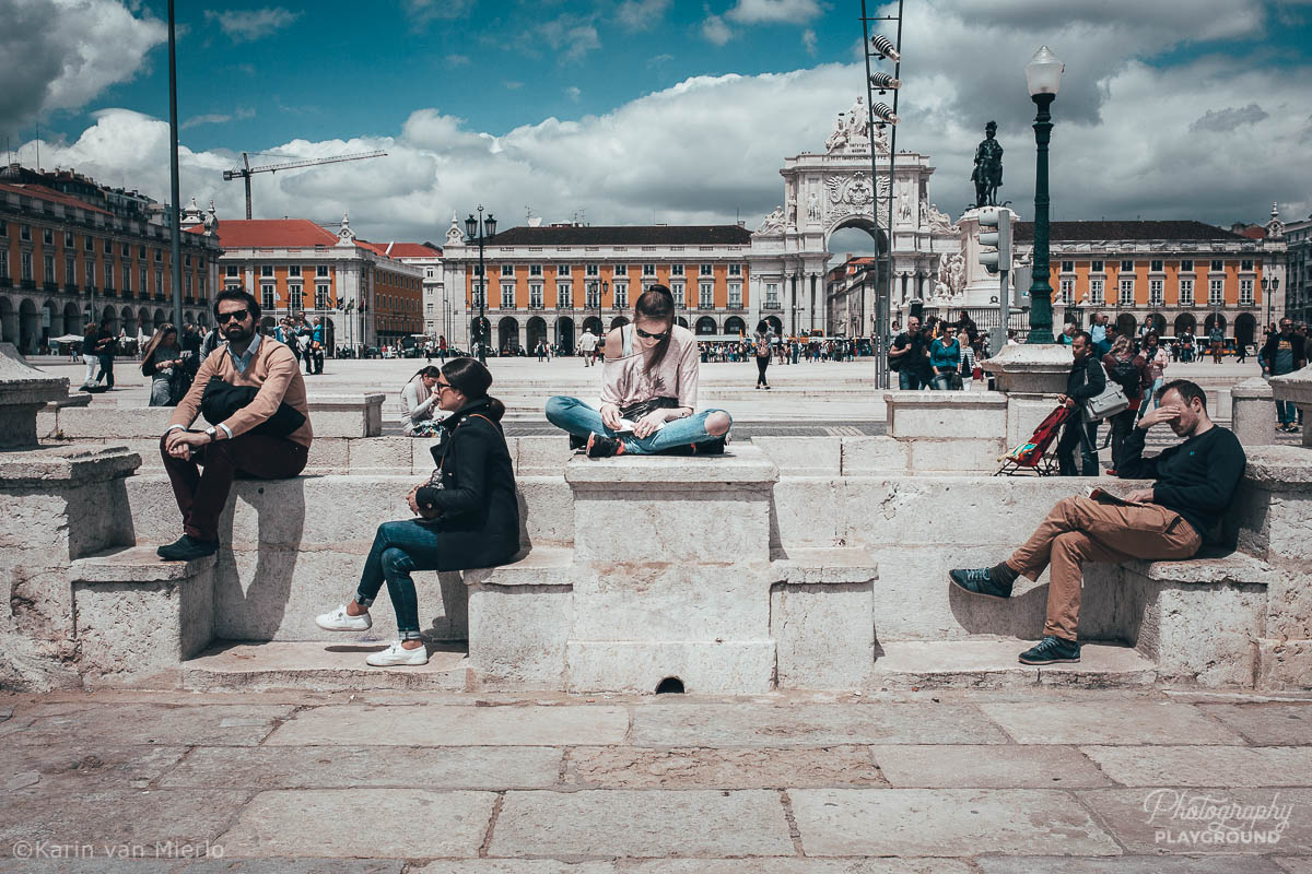 street photography ideas, street photography tips, how to start street photography, street photography cameras | Copyright Karin van Mierlo for Photography Playground. Photo: A girl reading a book at a busy square in Lisbon. Portugal.