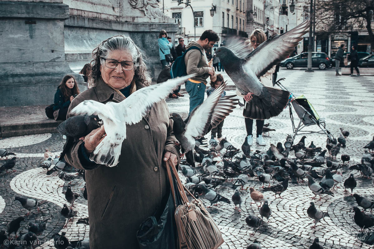 street photography ideas, street photography tips, how to start street photography, street photography cameras | Copyright Karin van Mierlo for Photography Playground. Photo: A woman feeding the pigeons at a square in Lisbon, Portugal.