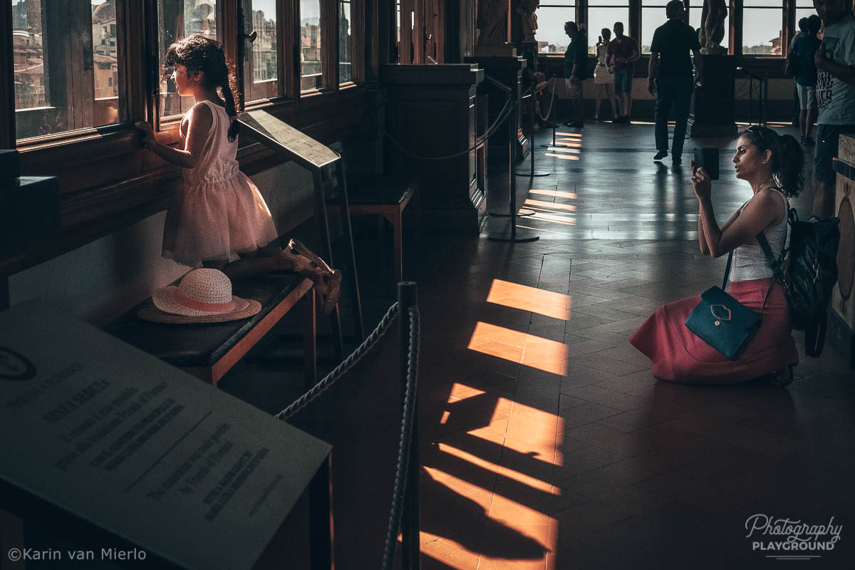 street photography ideas, street photography tips, how to start street photography, street photography cameras | Copyright Karin van Mierlo for Photography Playground. Photo: A mother taking pictures of her daughter at the Uffizi Gallery in Florence, Italy.