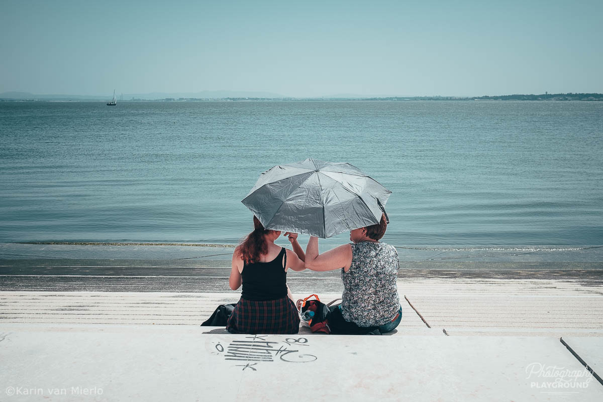 candid street photography ideas, street photography tips, how to start street photography, street photography cameras | Copyright Karin van Mierlo for Photography Playground. Photo: two women talking under an umbrella at the river Tagus in Lisbon, Portugal.