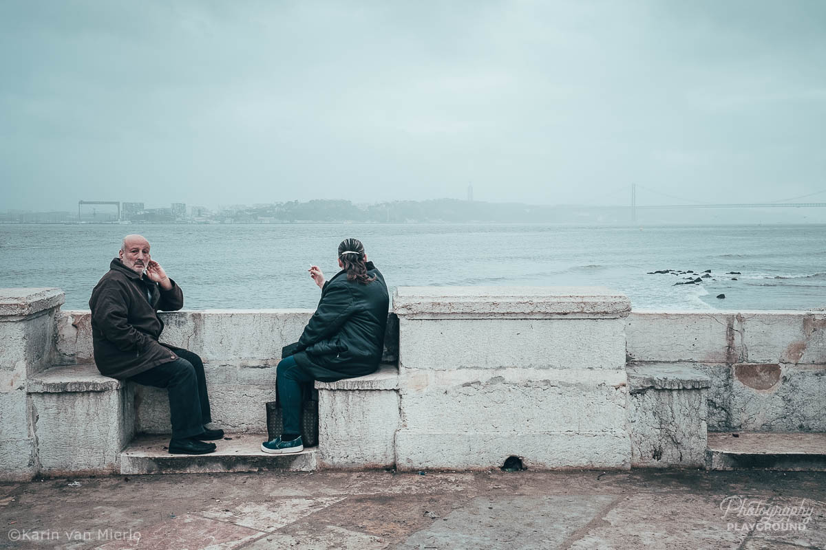 street photography ideas, street photography tips, how to start street photography, street photography cameras | Copyright Karin van Mierlo for Photography Playground. Photo: A man and a woman sitting on a bench at the riverbank of the Tagus, Lisbon, Portugal.