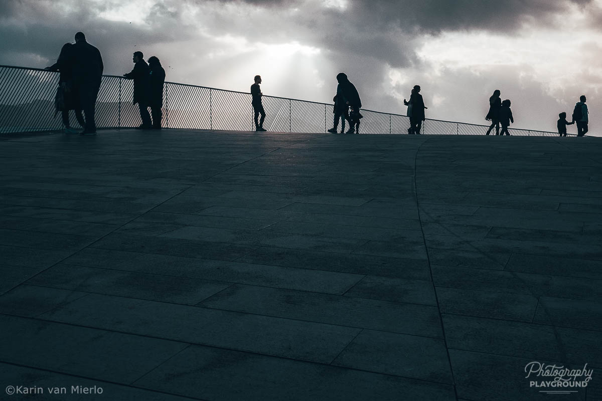 street photography ideas, street photography tips, how to start street photography, street photography cameras | Copyright Karin van Mierlo for Photography Playground. Photo: silhouettes of people on the roof of the MAAT museum in Lisbon, Portugal.