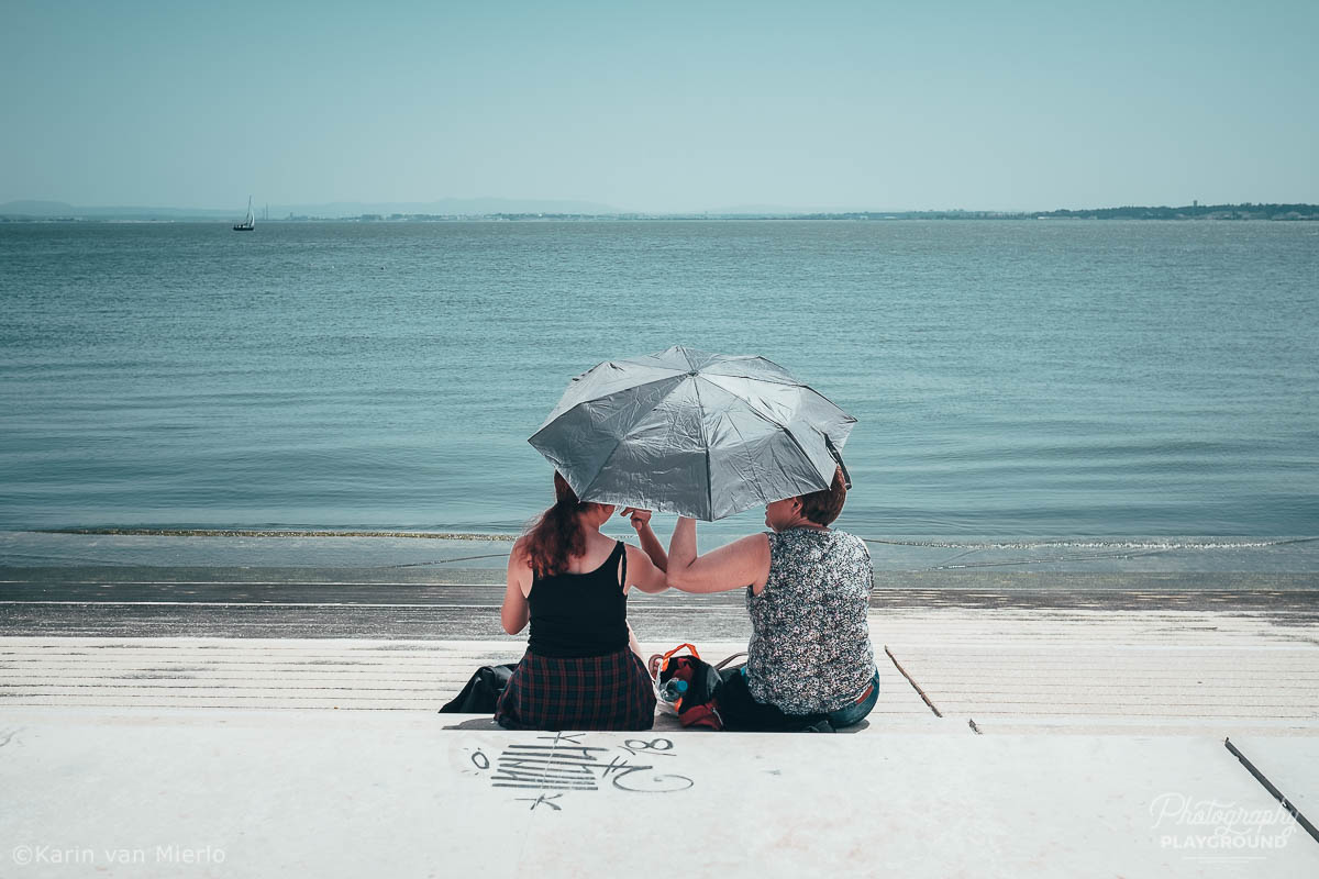 how to choose a camera | Photo: 2 people sitting under an umbrella at the Tagus riverbanks in Lisbon, Portugal ©Karin van Mierlo, Photography Playground