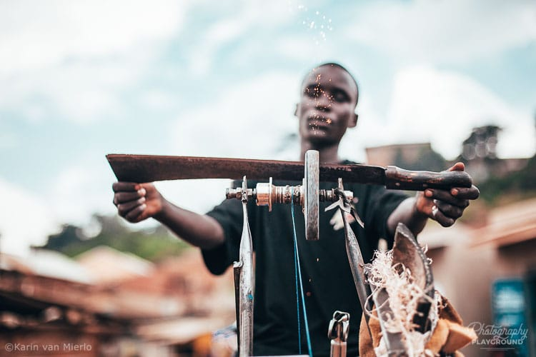 Photography Mentoring Sessions | Photo ©Karin van Mierlo | Photography Playground | A man sharpening a machete in Acholi Quarter, Kampala Uganda.